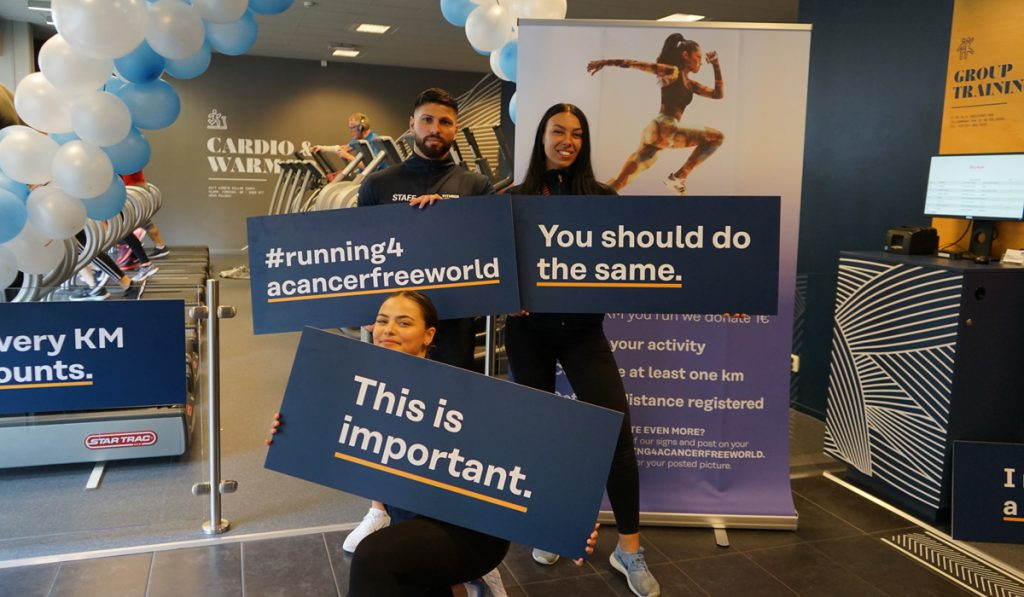 Fitness24Seven staff posing with signs and powerful messages for a cancer free world